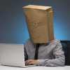 Man with a cardboard box on his head working on laptop